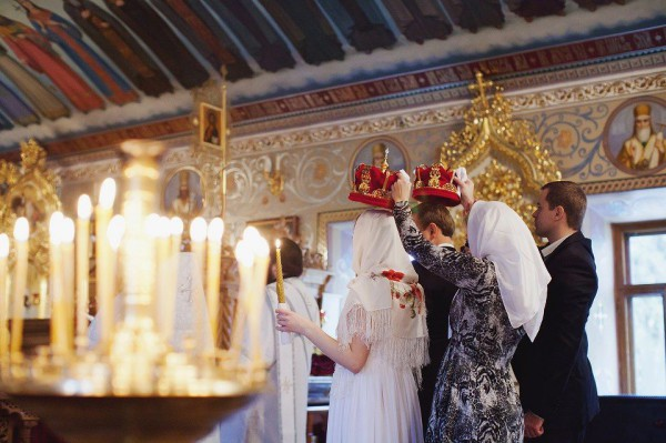 a young couple at a church wedding, witnesses hold crowns over their heads