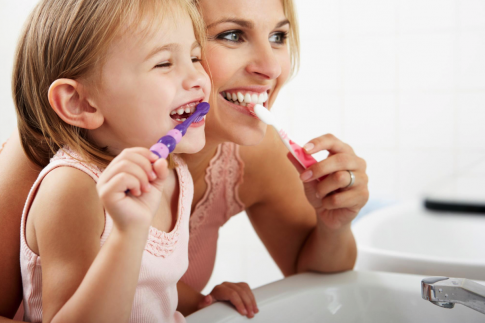Mom and daughter brush their teeth